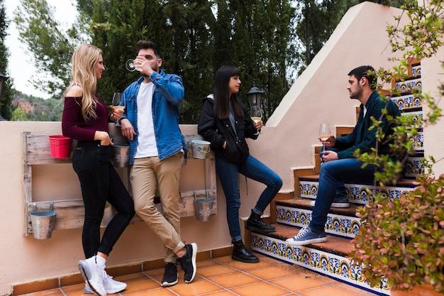 Молодые друзья, выпивая, сидя на лестнице