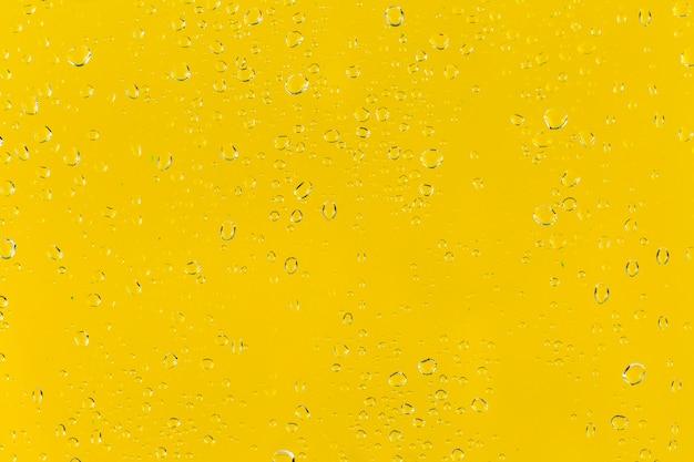 Капли воды на желтой поверхности