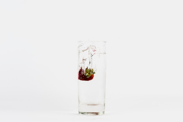 Клубника, падающая в стакан воды