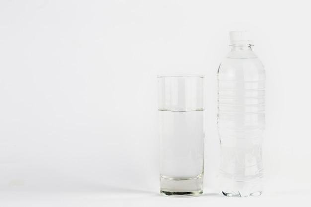 透明な水を入れたガラスとボトル