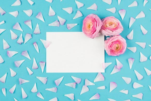 Пустая записка с цветами и лепестками вокруг