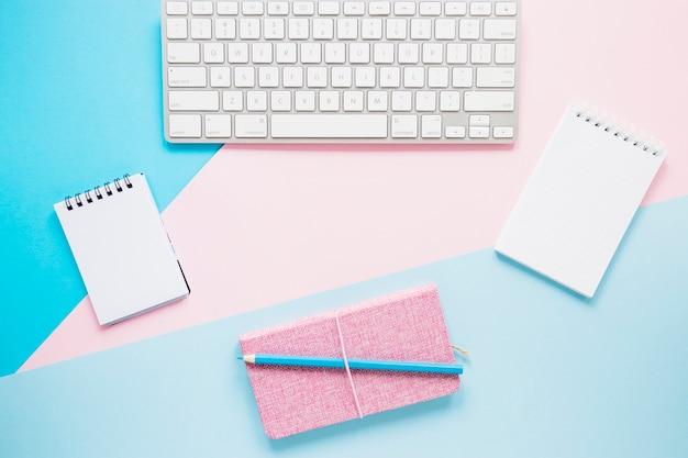 居心地の良いデスクトップ上のキーボードとノート