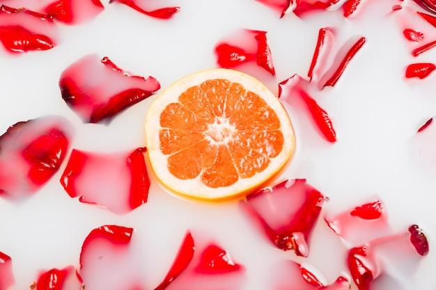 Ломтик грейпфрутов и лепестков цветов, плавающих на чистой белой воде