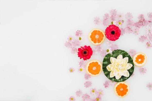グレープフルーツスライスと様々な花で飾られたバスミルクの高い角度のビュー
