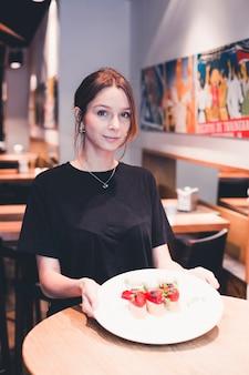 Официантка, держащая табличку с тартинами
