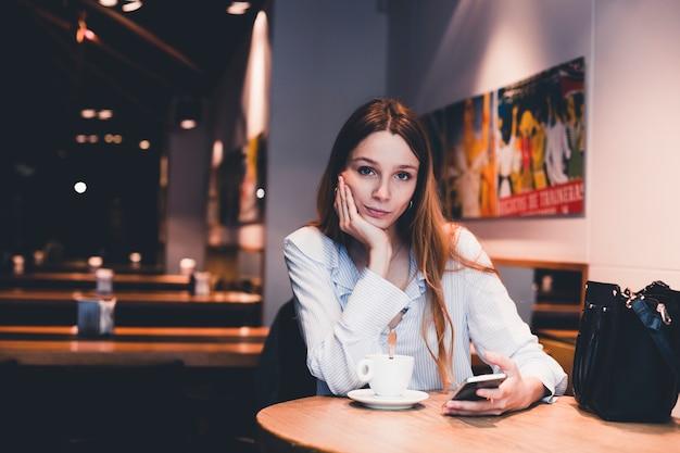 カメラを見てスマートフォンを持つ退屈な女性