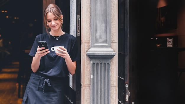 Улыбающаяся официантка с напитком, использующим смартфон