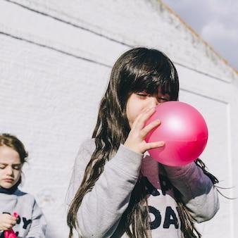 女の子が風船を吹く