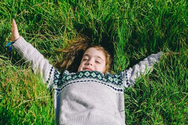 Симпатичная девушка, лежа на траве
