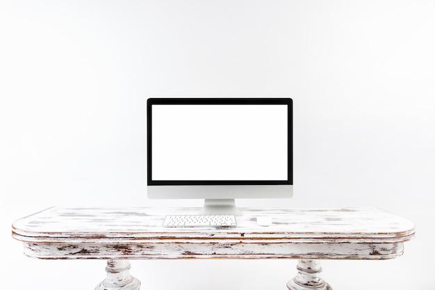 ヴィンテージの机の上に立つ最小限のコンピュータ