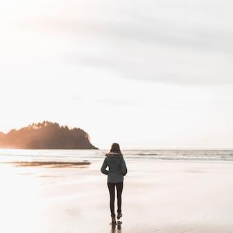 海に向かって歩く若い女性