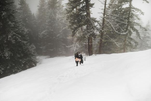雪の上を歩く薪の人