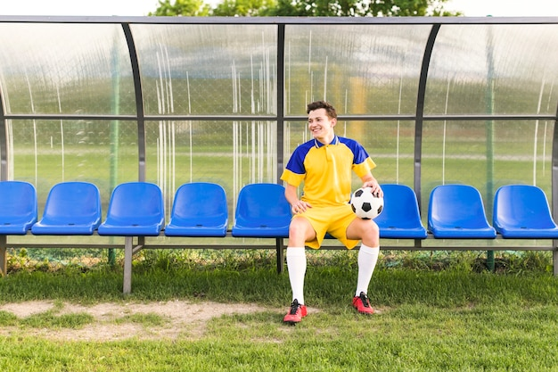 ベンチ上の男とアマチュアフットボールのコンセプト
