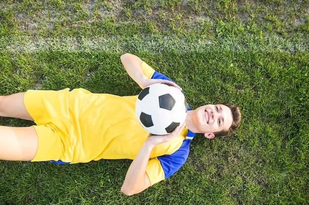 ボールを投げる横たわった男とアマチュアフットボールのコンセプト