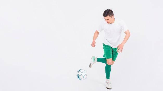 ボールで走っているサッカー選手
