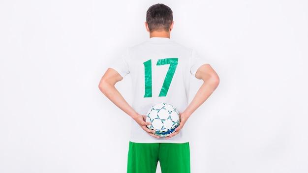 後ろにボールを持っているサッカー選手