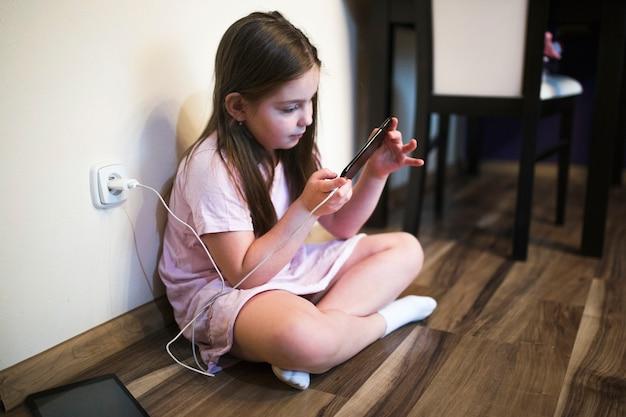 スマートフォンを充電している少女