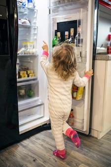 冷蔵庫から食べ物を選ぶ匿名の少女