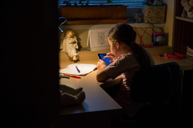 女の子は勉強する代わりにゲームをしています