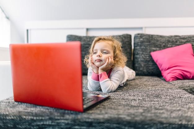 Скучающая девушка смотрит фильм на ноутбуке