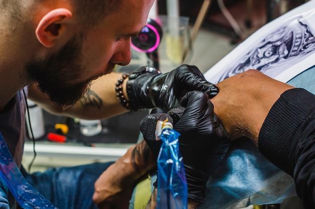 ひげをつけたタトゥーアーティストが働いています