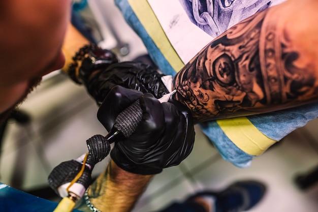 Мастер рисования татуировки на руке