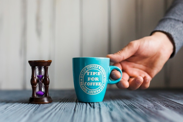 テーブルからコーヒーカップを取る手