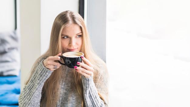 Женский пить кофе, сидящий у окна
