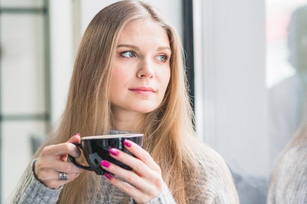 Красивая женщина с кофе, глядя на окно