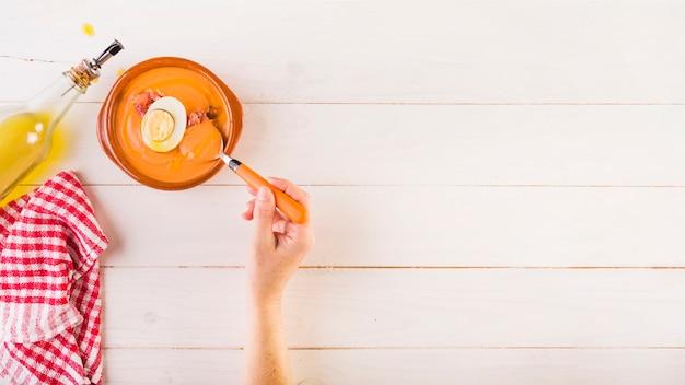 Рука с ложкой с супом на кухонном столе