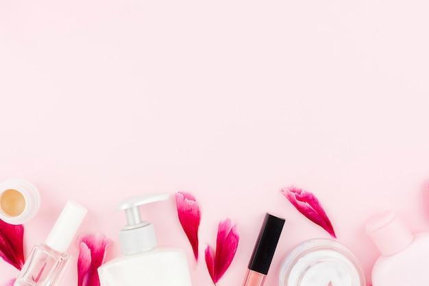 ピンクの化粧品と花びらのセット