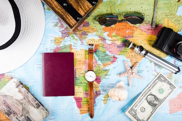 世界地図上の海の殻、紙幣、パスポート、アクセサリー