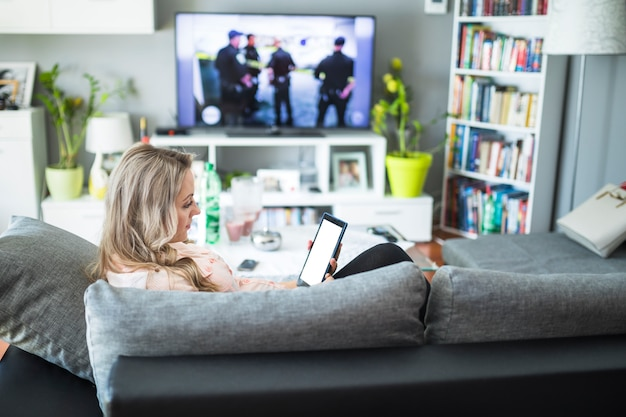 Беременная женщина, используя цифровой планшет в гостиной
