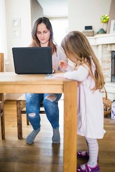 ラップトップを使用して彼女の母親の前で学習女の子