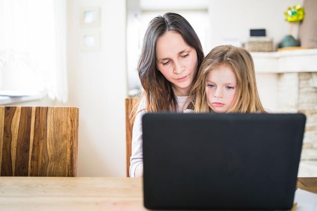 彼女の娘と母親の前でラップトップのクローズアップ