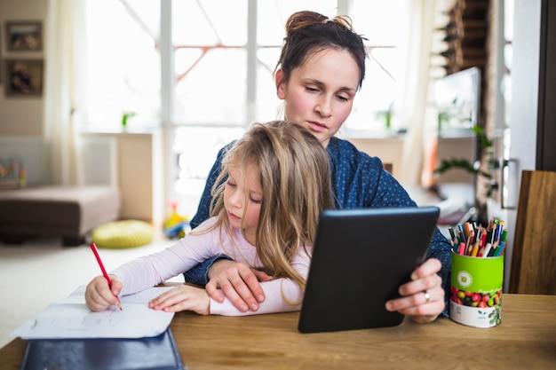 娘が宿題をしている間にデジタルタブレットを使用している女性