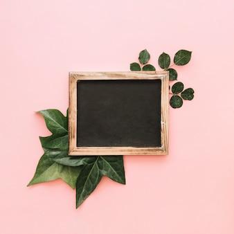 Повышенный вид сланца над тропическими листьями на розовой поверхности