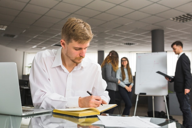 職場でペンで日記のスケジュールを書くビジネスマン