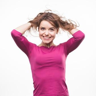 白い背景に彼女の毛で遊んでいるかわいい笑顔の若い女性