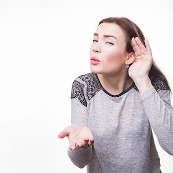 Молодая женщина, слушая ее руку на ухе на белом фоне