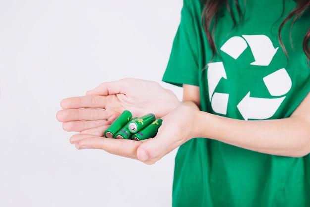 緑色の電池を持っている女性の手のクローズアップ