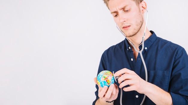聴診器で地球儀を診断する若い男
