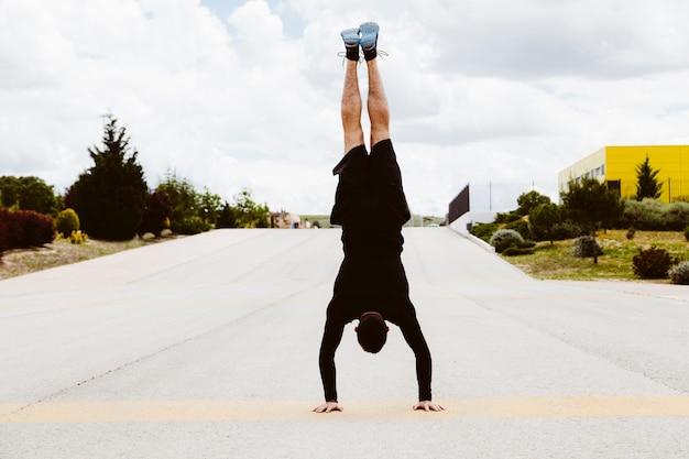 通りに逆立ち運動をしている男