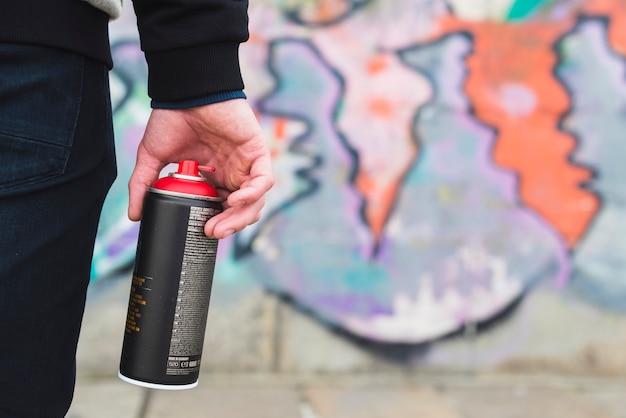 Аэрозольная аэрозольная бутылка в руке художника