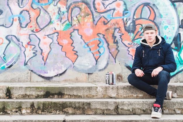 落書きの壁の前に座っている男