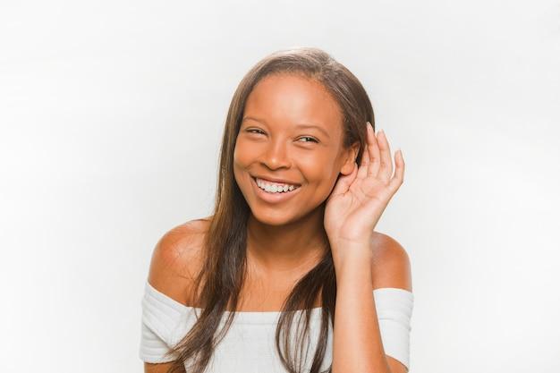 白い背景で聞くことを試みている笑顔の十代の少女