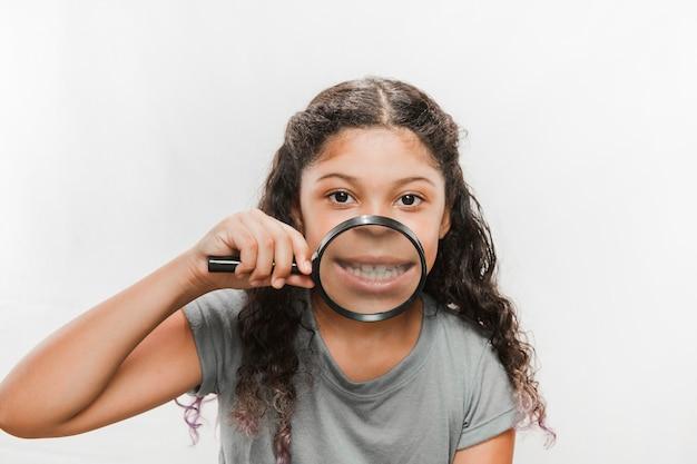 Крупный план девушка с увеличительным стеклом, показывая ее зубы