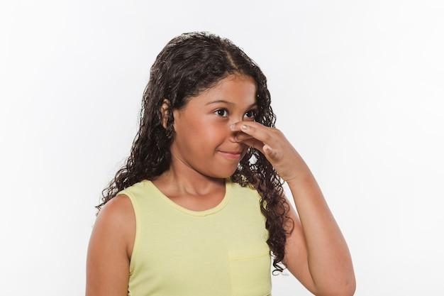 悪臭のために彼女の鼻を覆う女の子のクローズアップ
