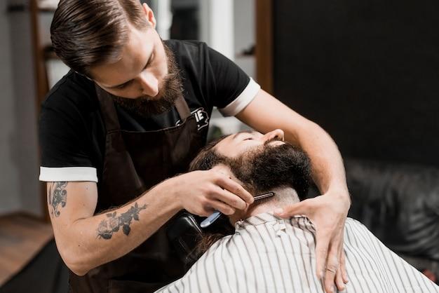 剃刀で男のひげを切る理髪師