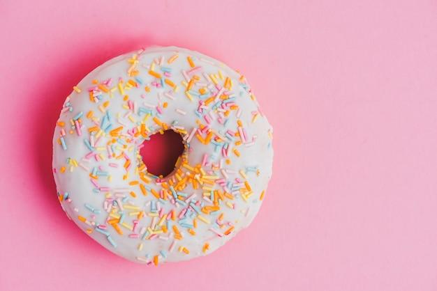 ピンクの背景に散らばった釉薬入りドーナツ